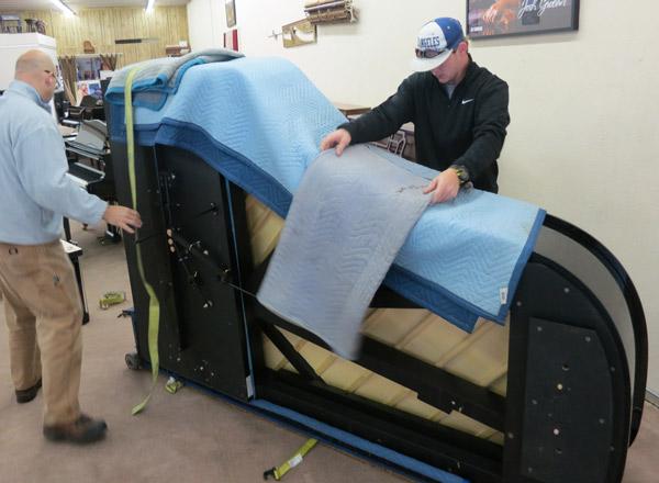 Рояль тщательно упаковывается перед переноской. Используются ремни и полозья для бережной транспортировки.